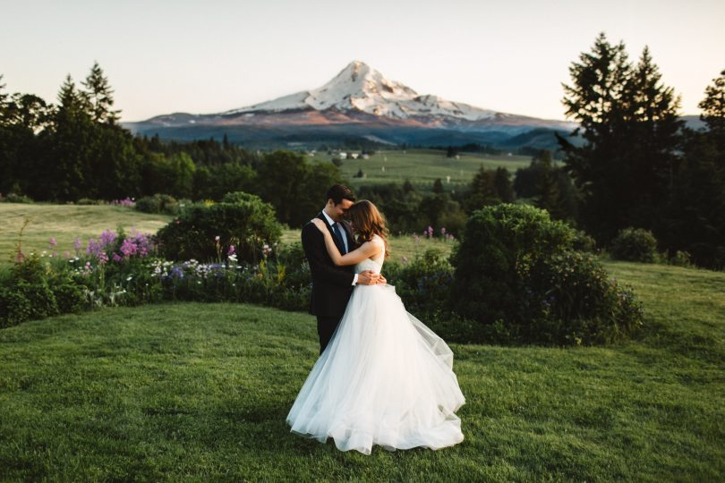 A wedding couple poses in front of Mt Hood on their wedding night