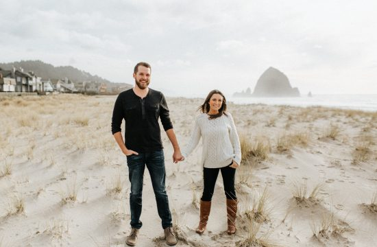 A couple holds hands on canon beach during their engagement session