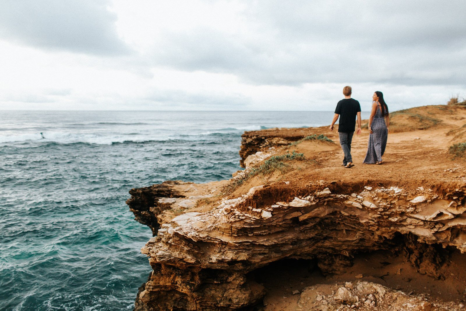 A couple walks along the coast of Kauai