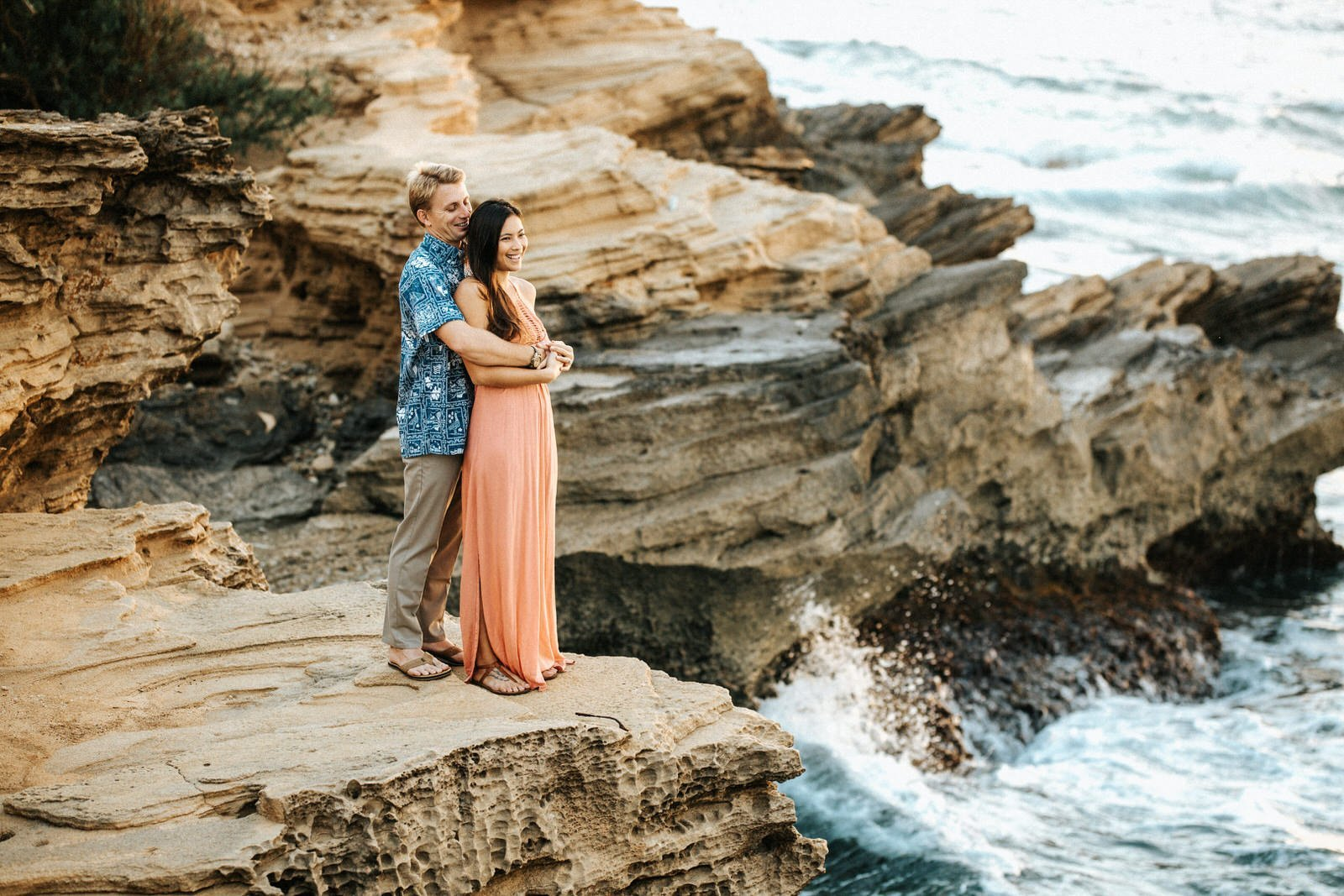 A couple watches the Ocean at sunrise during their engagement session in Kauai