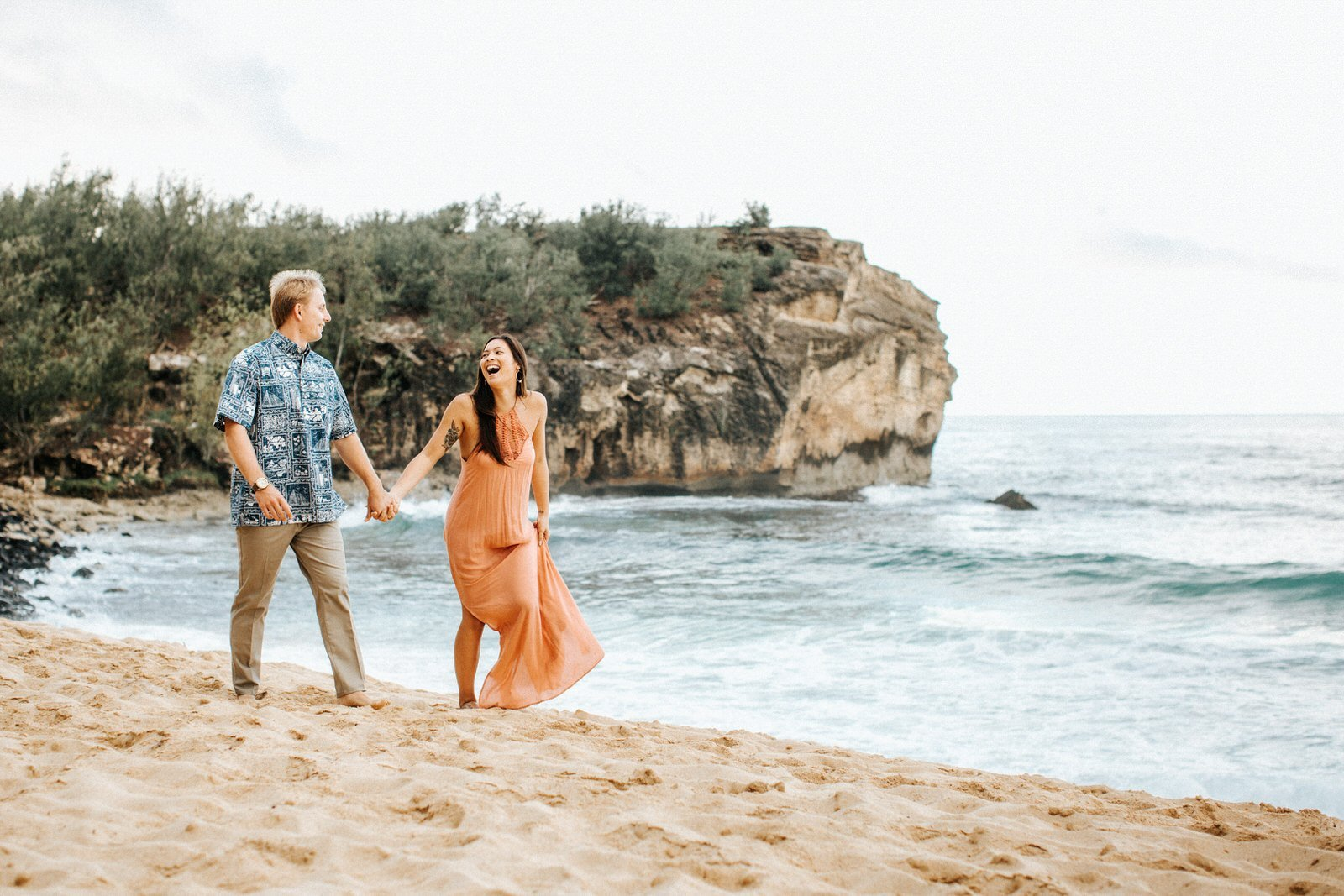 A young couple laughs during their engagement session on the beach