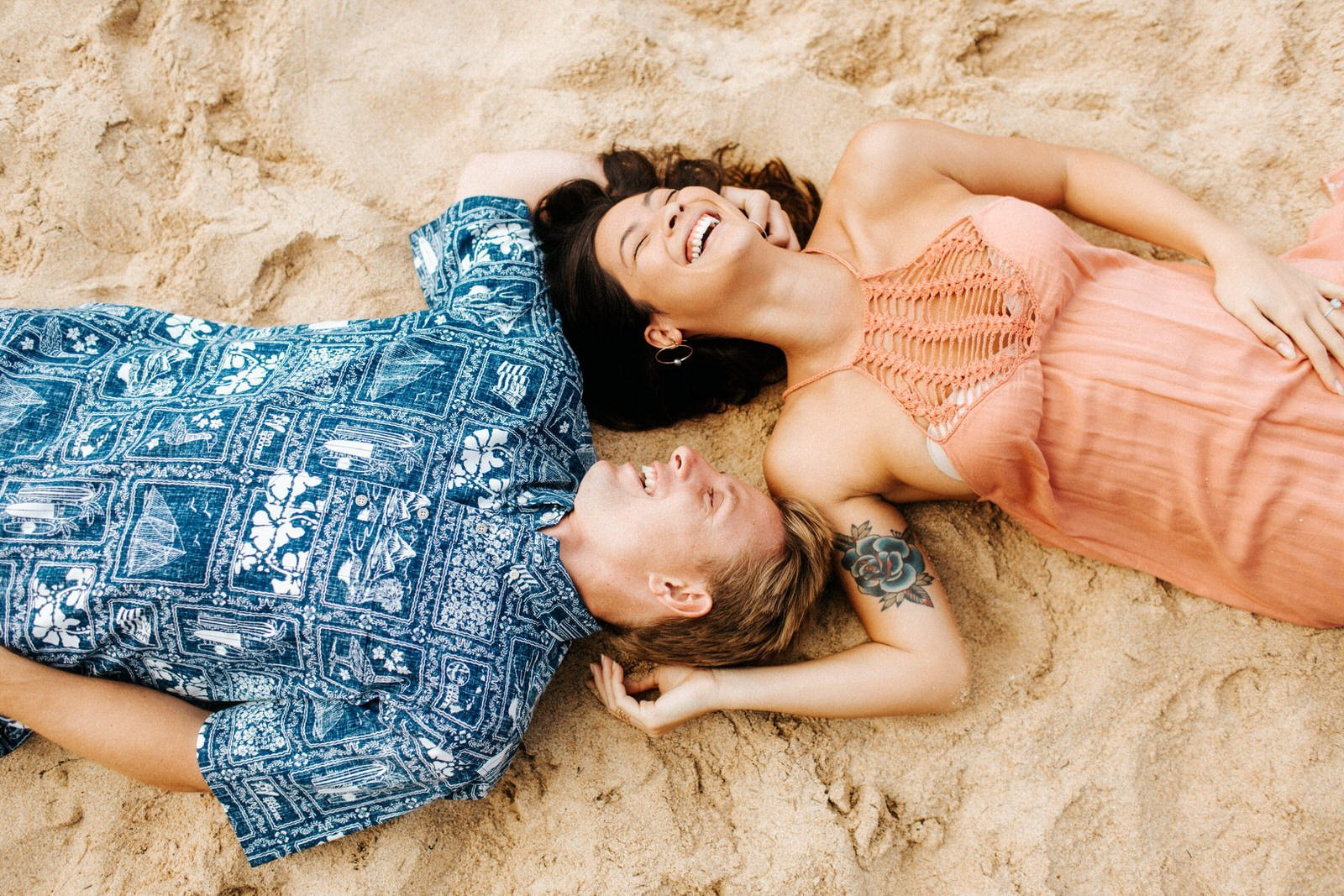 A young couple laughs on the beach