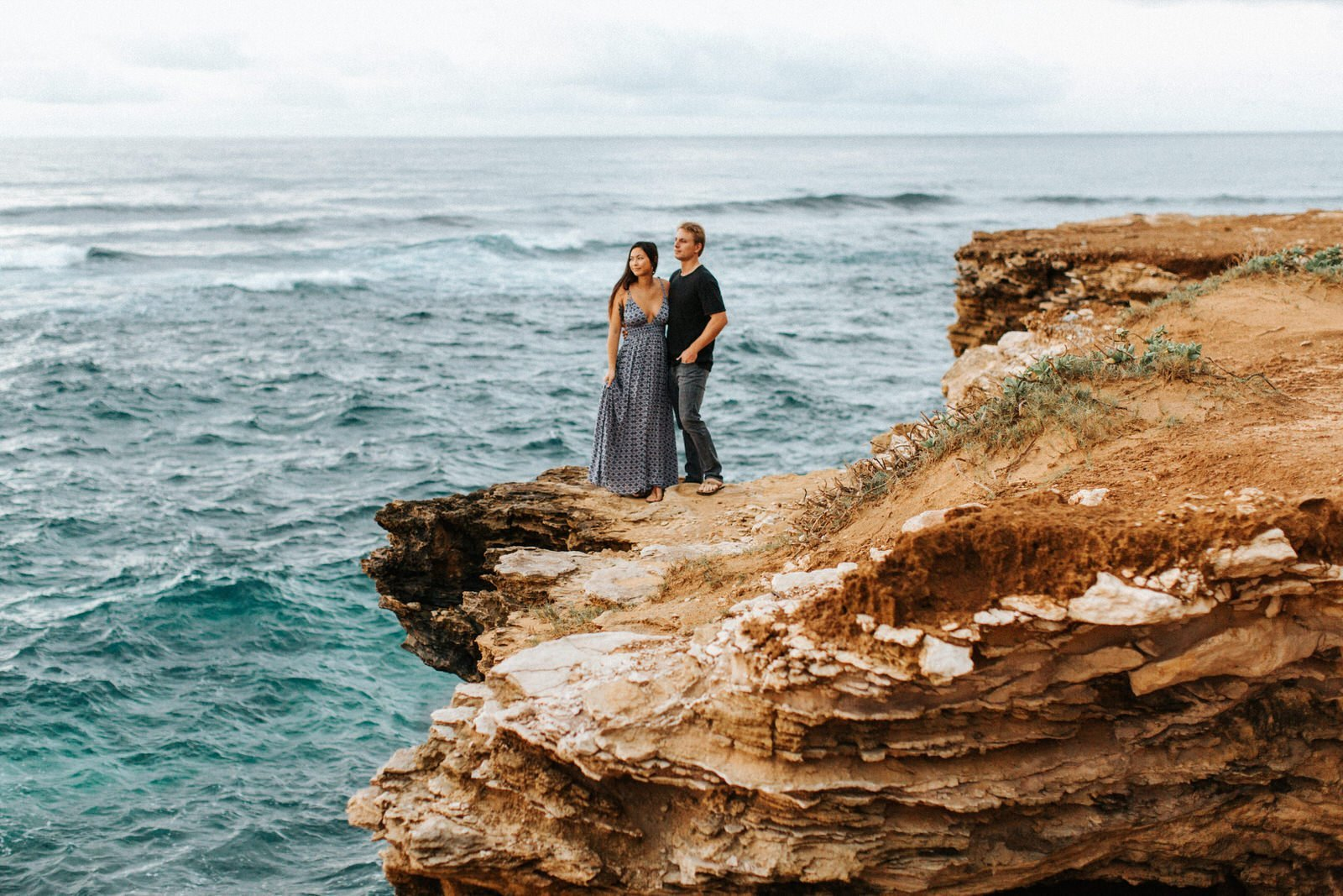 A couple watches the sunrise during their Kauai engagement session