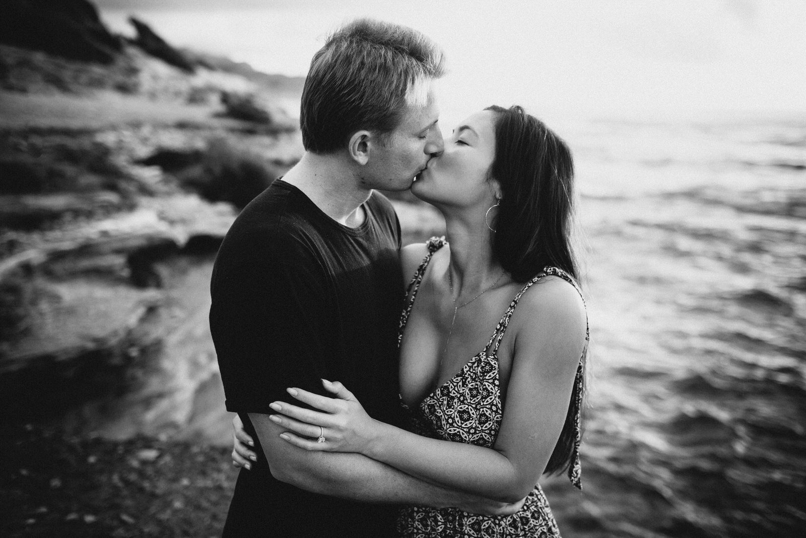 A young couple kisses during an engagement session in Kauai