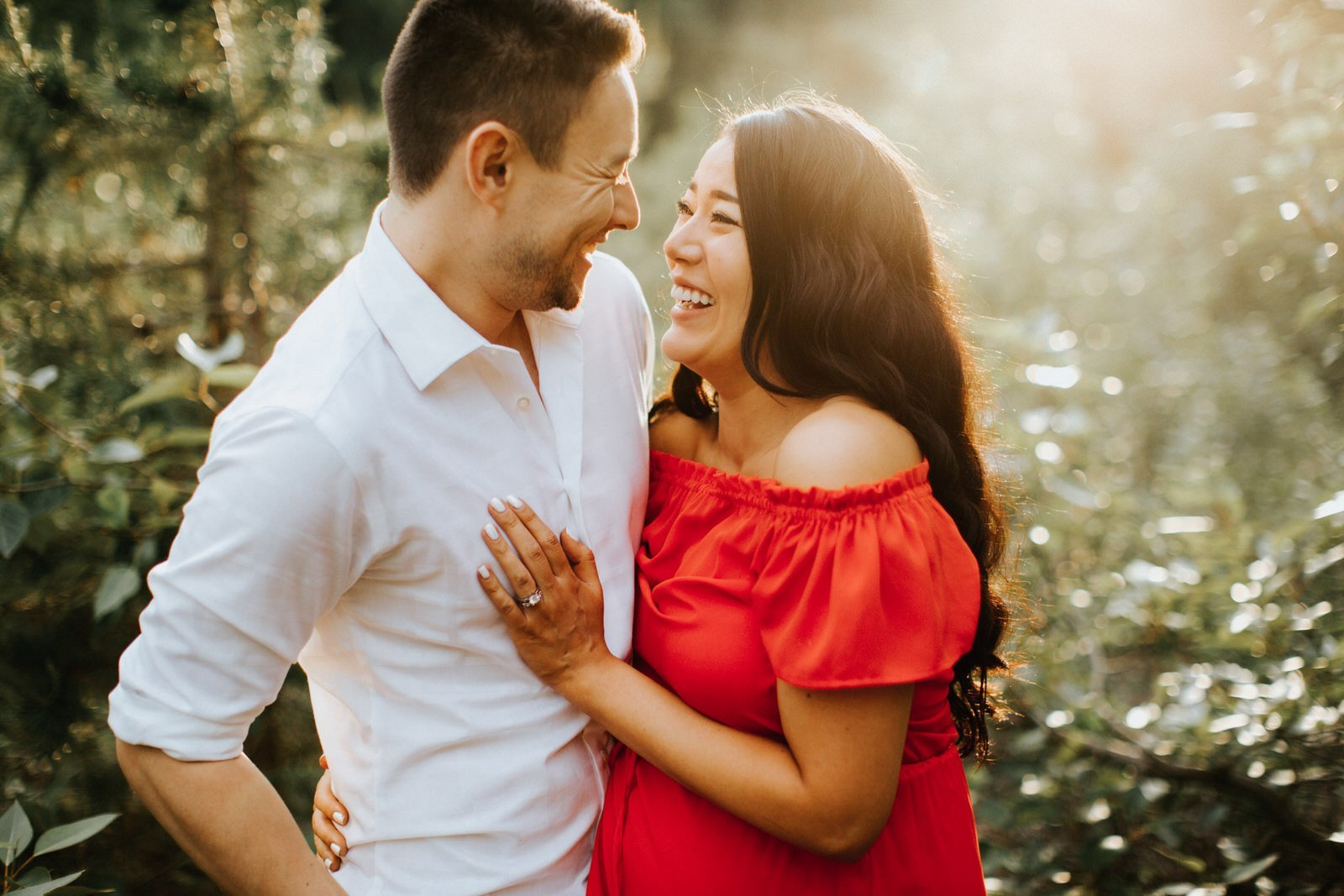 A couple laughs during their engagement session