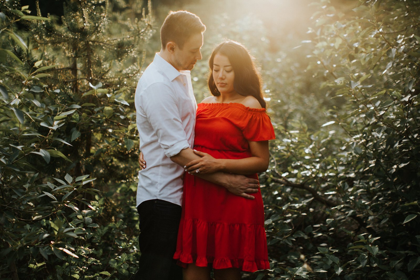 A woman in a red dress cuddles with her husband during an engagement session