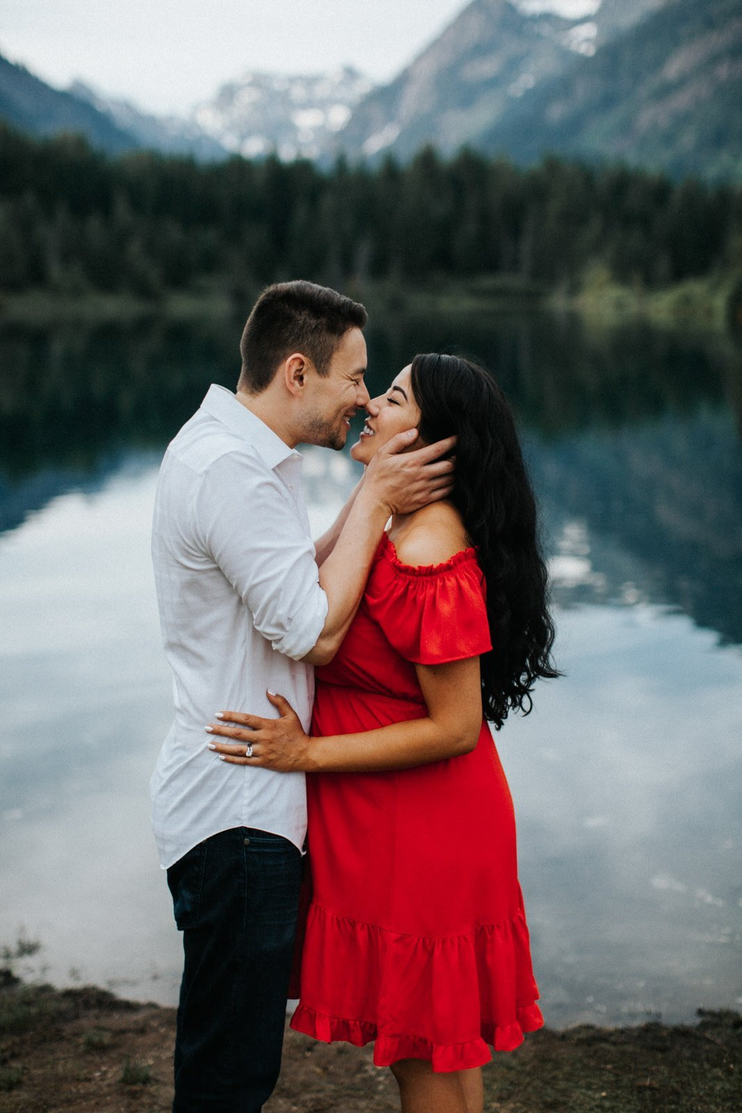 A couple laughs and kisses during their engagement session at a pnw mountain lake