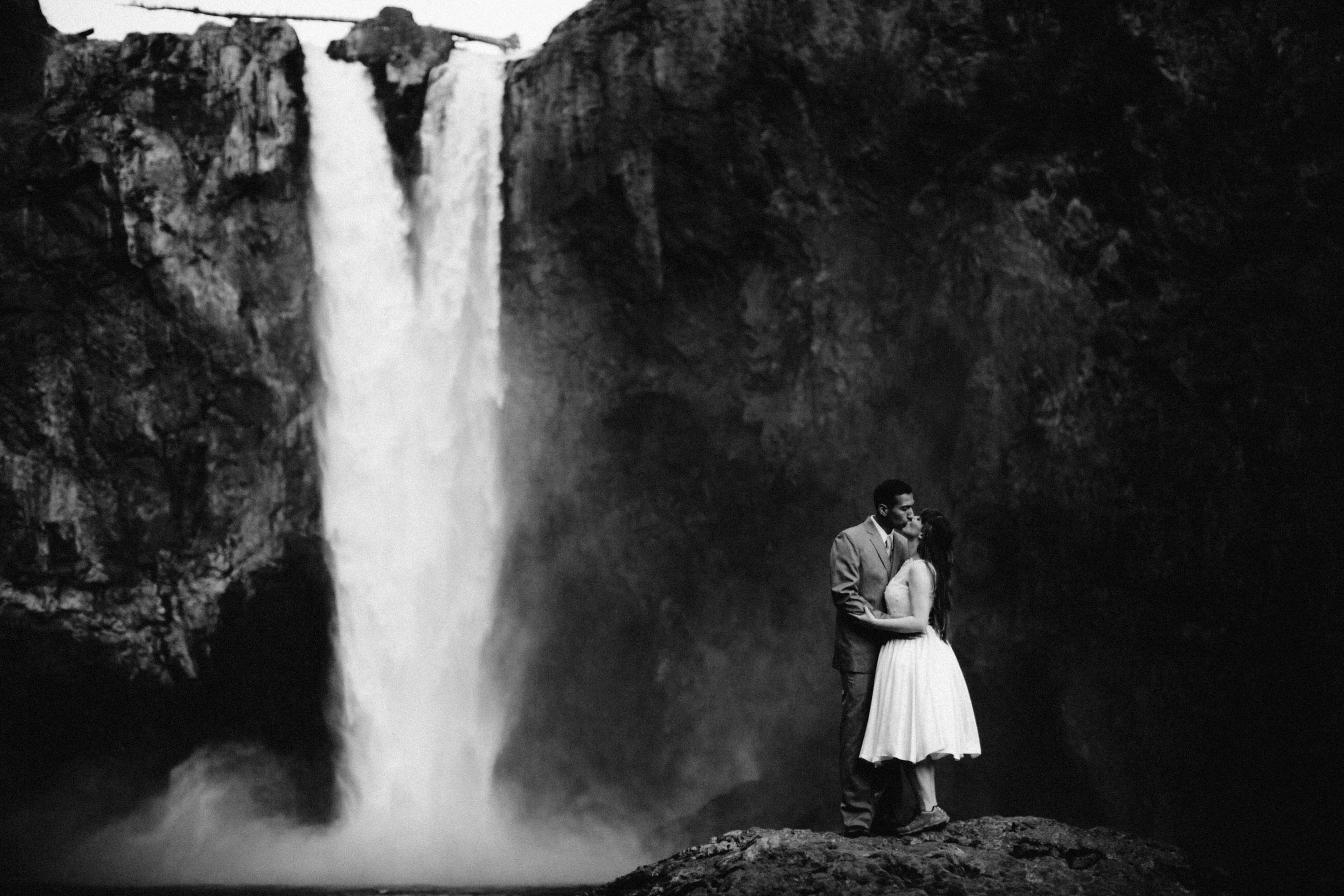 A couple stands at snoqualmie falls during their engagement photo session