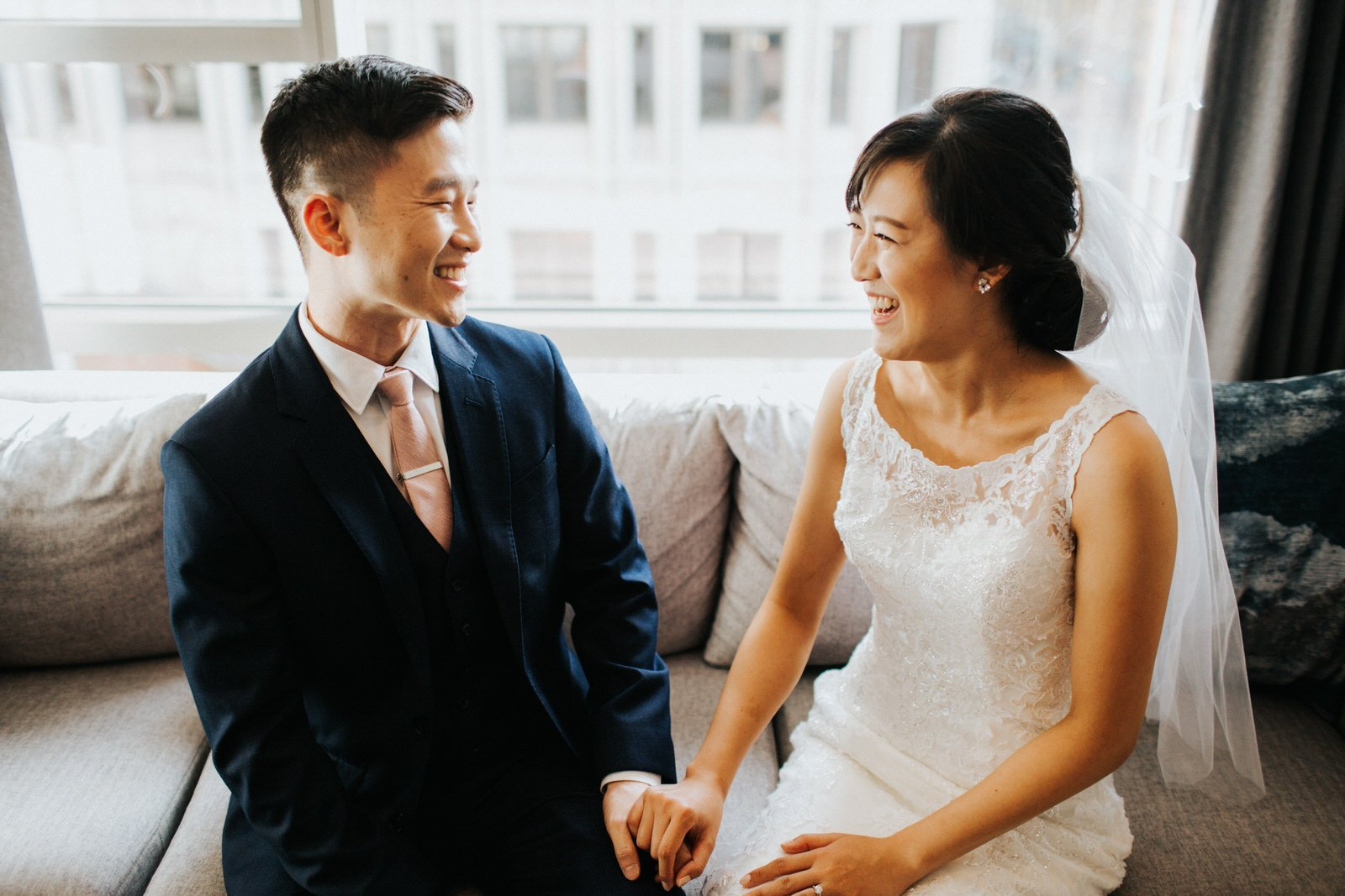 The couple sits on a couch and smiles at each other