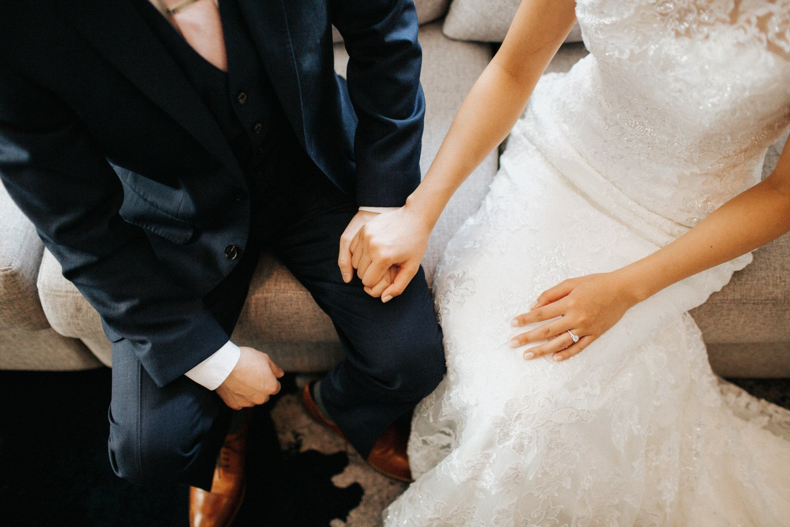 The couple holds hands on a couch
