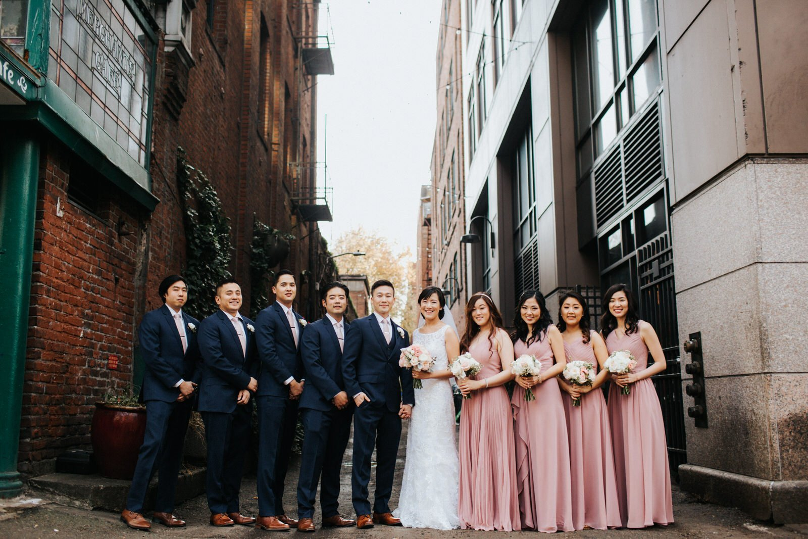 Wedding party poses in an alley at pioneer square