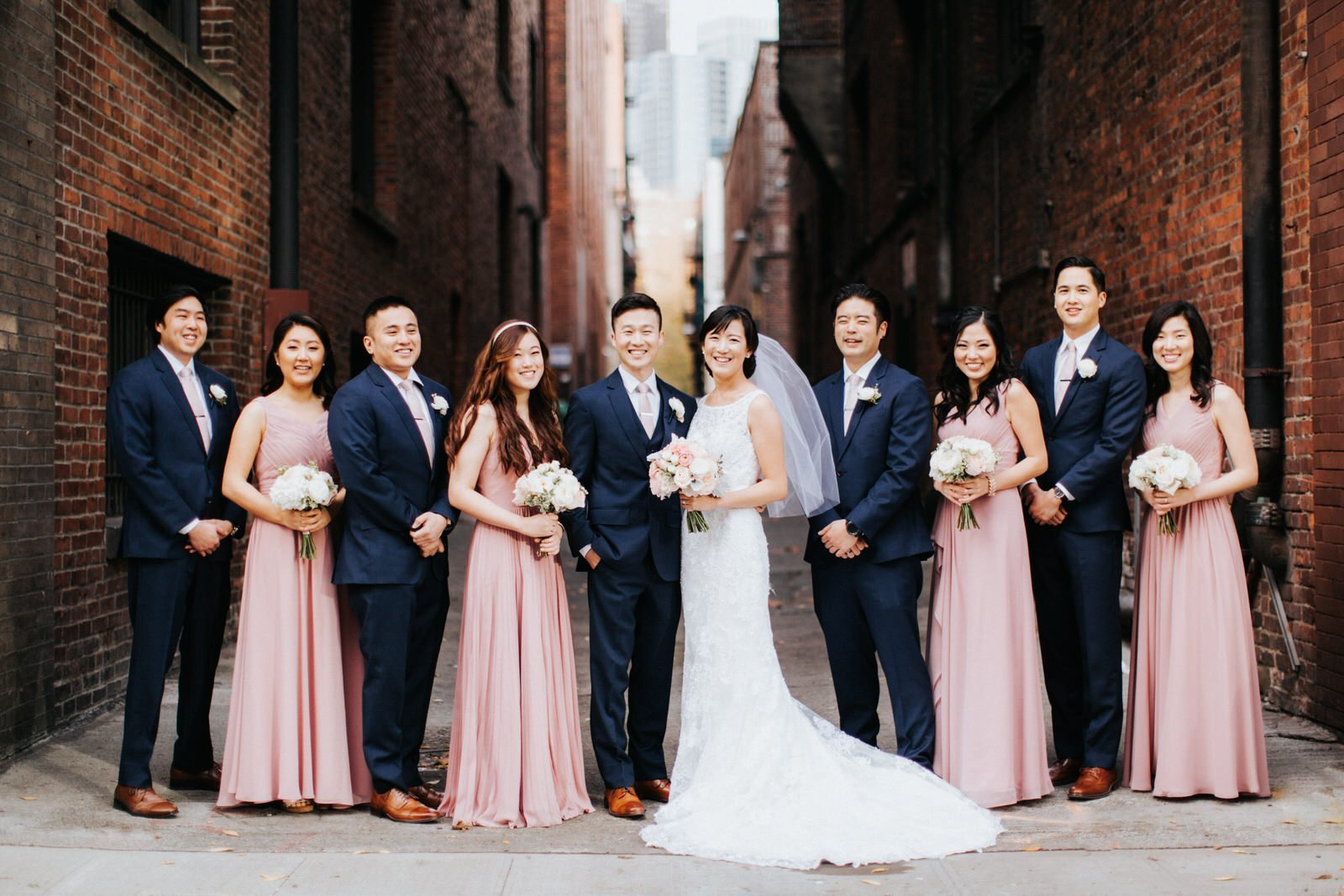 The wedding party poses in an alleyway in pioneer square