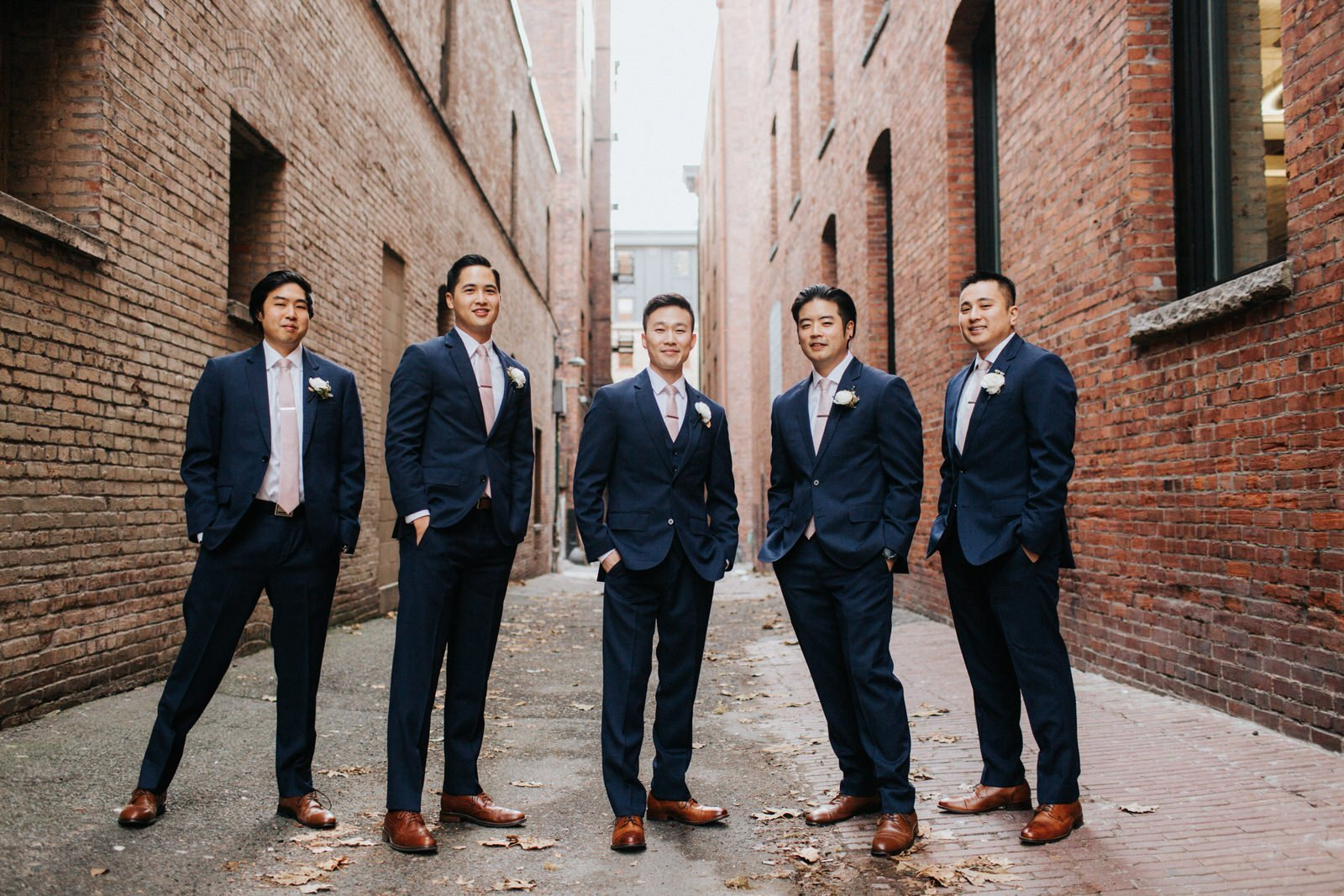 The groomsmen pose in an alley in pioneer square