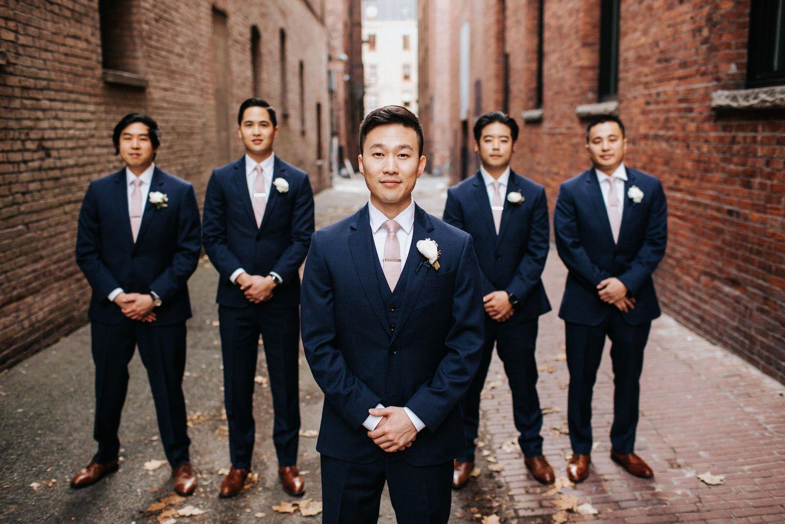 The groomsmen pose in pioneer square before their wedding