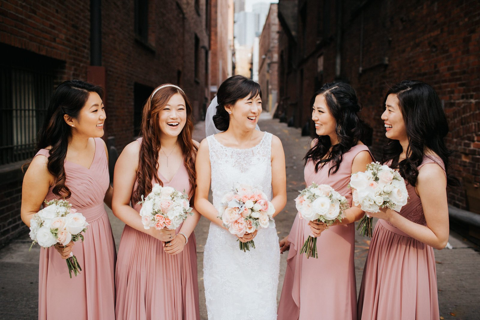 The bridesmaids laugh during photos in an alleyway in pioneer square