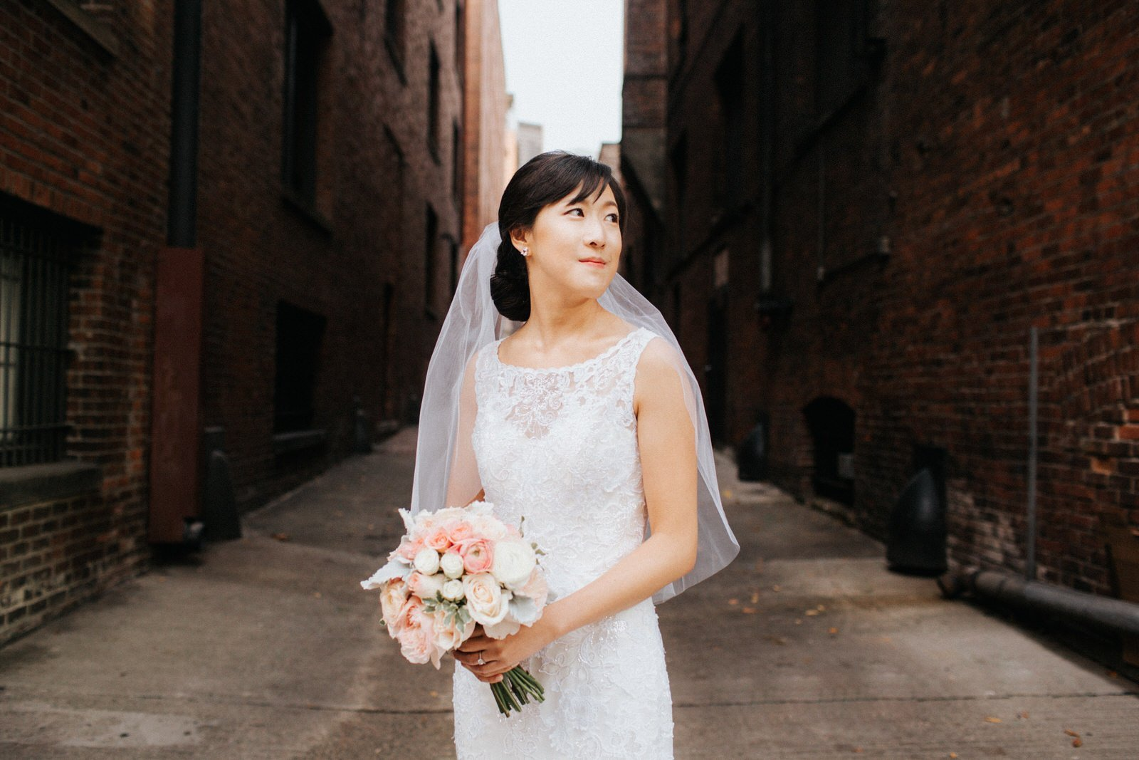 The gorgeous bride poses in pioneer square in a veil