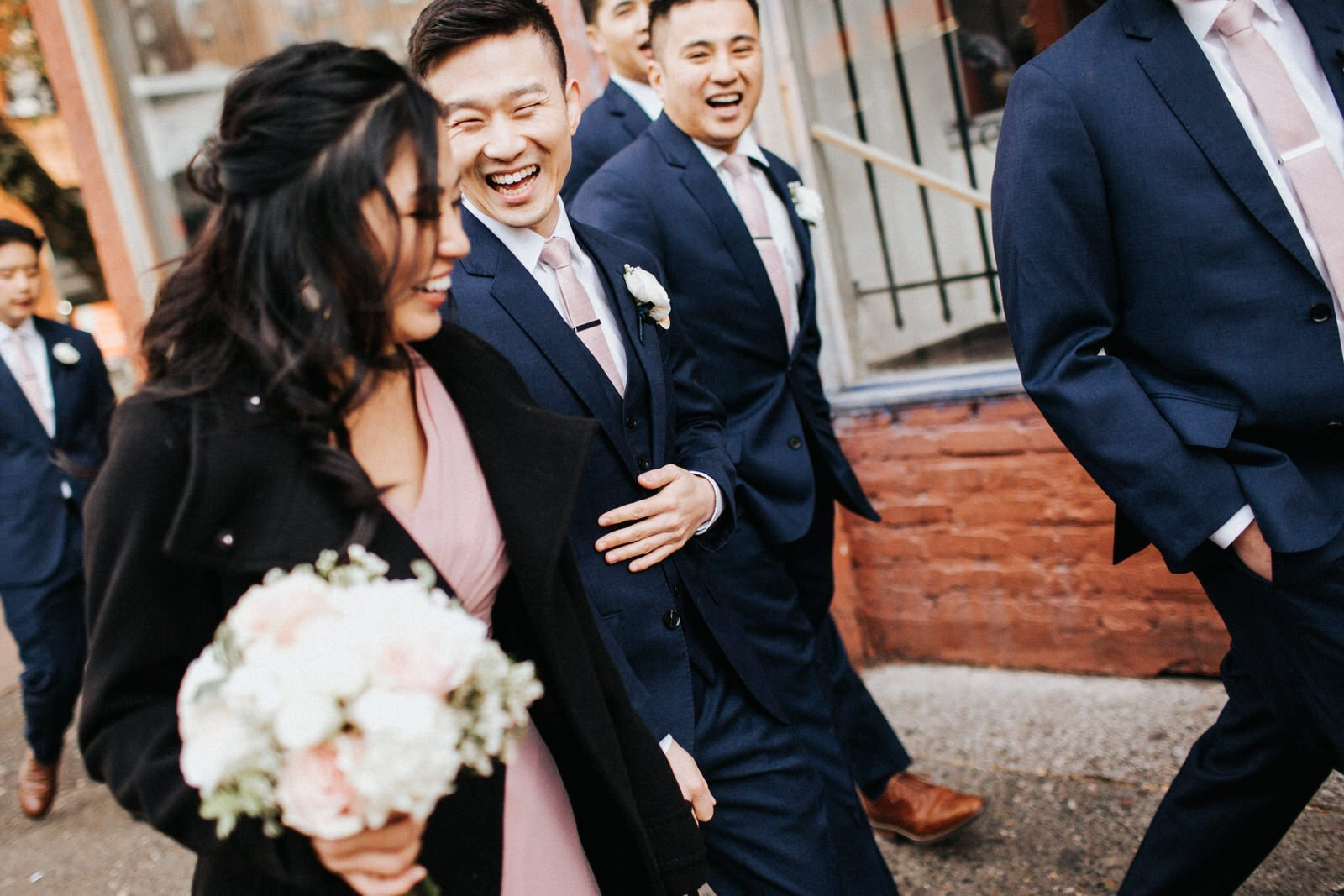 The groom laughs with the bridesmaids
