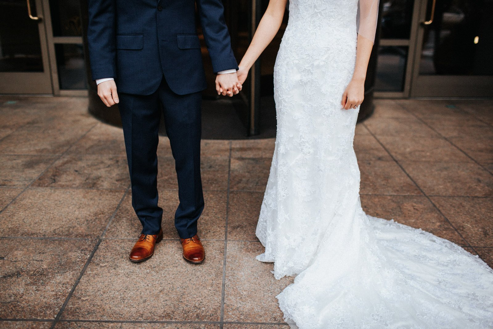 The couple poses in front of hotel 1000 in downtown seattle