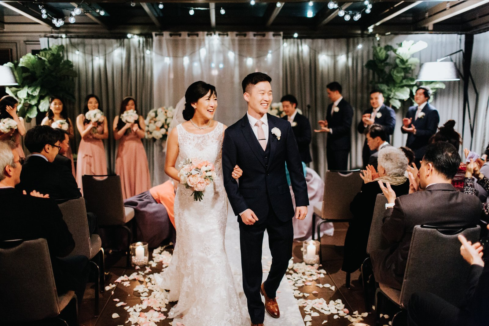 The couple walks down the isle during their night ceremony at hotel 1000