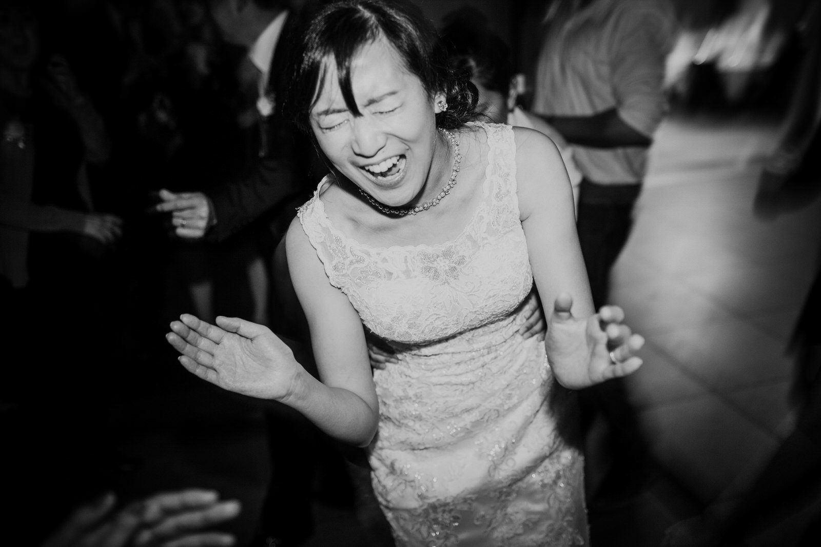 The bride laughs during the dancing at her reception