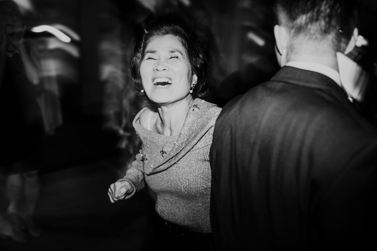 Guests laugh while dancing at the reception