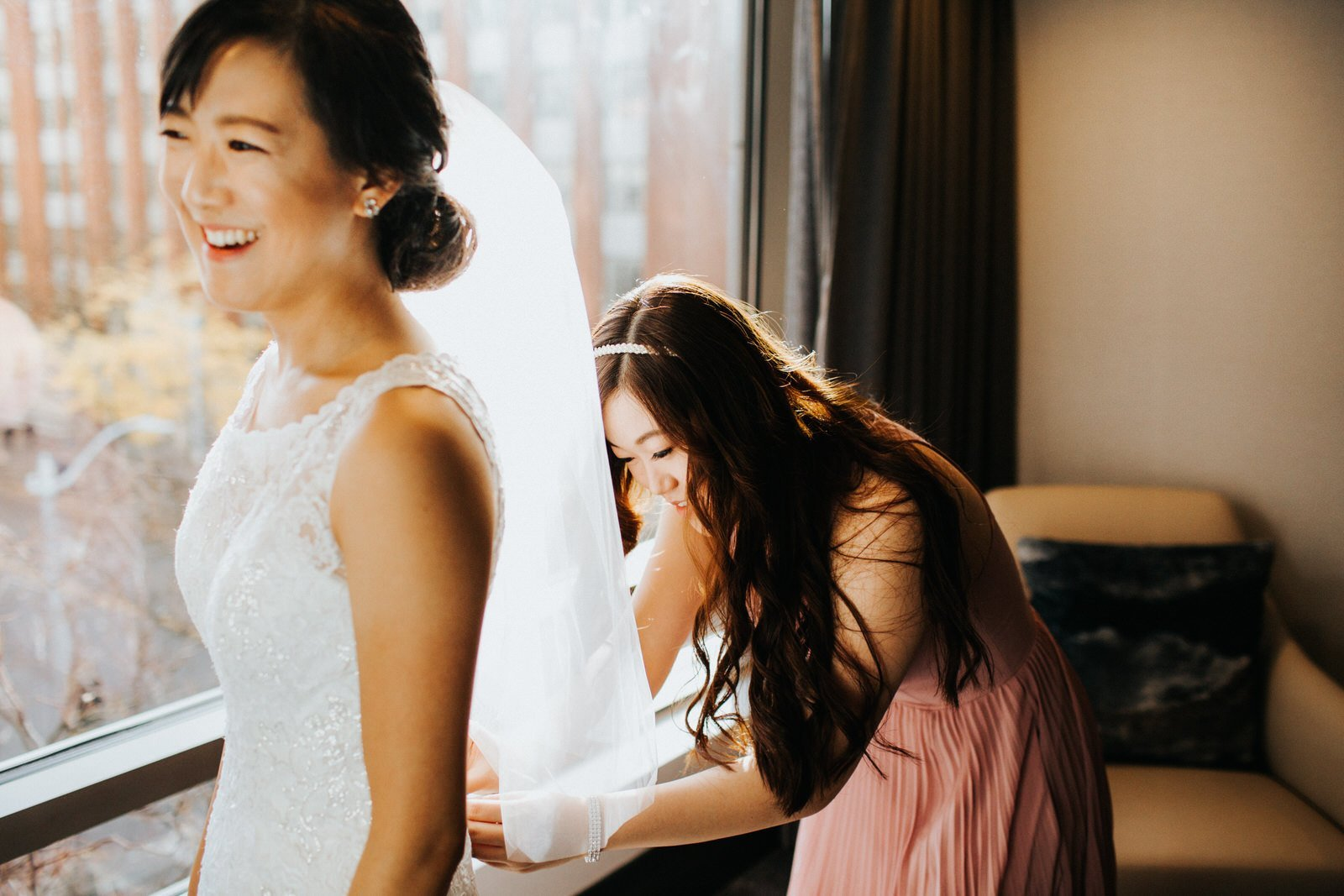 Maid of honor helps the bride into her dress