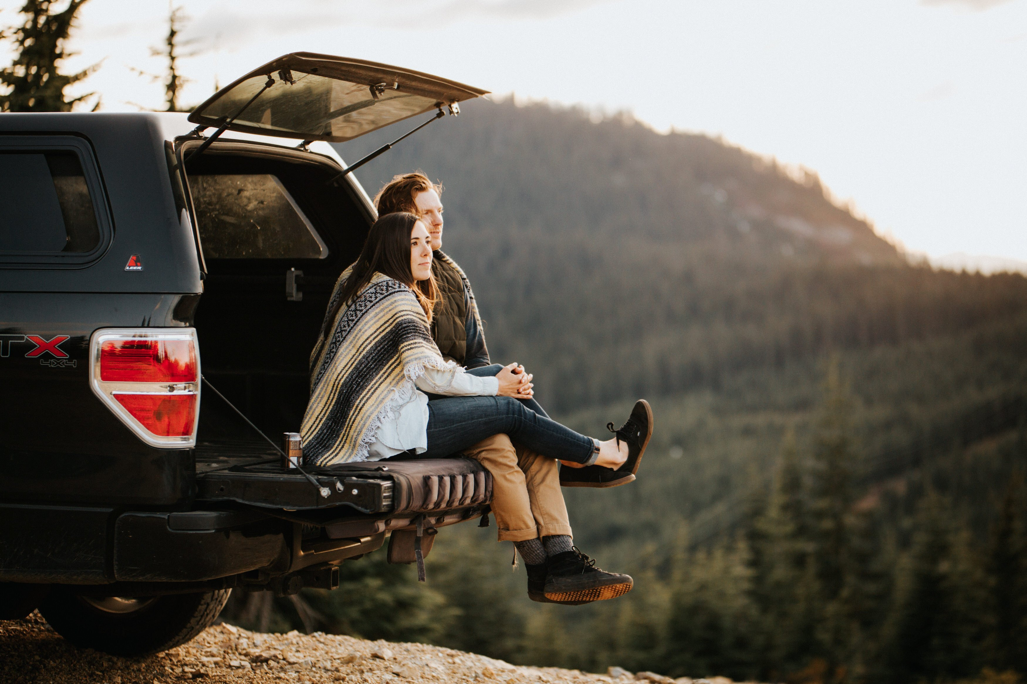 A couple sits in the back of their truck during their pnw engagement session in the mountains