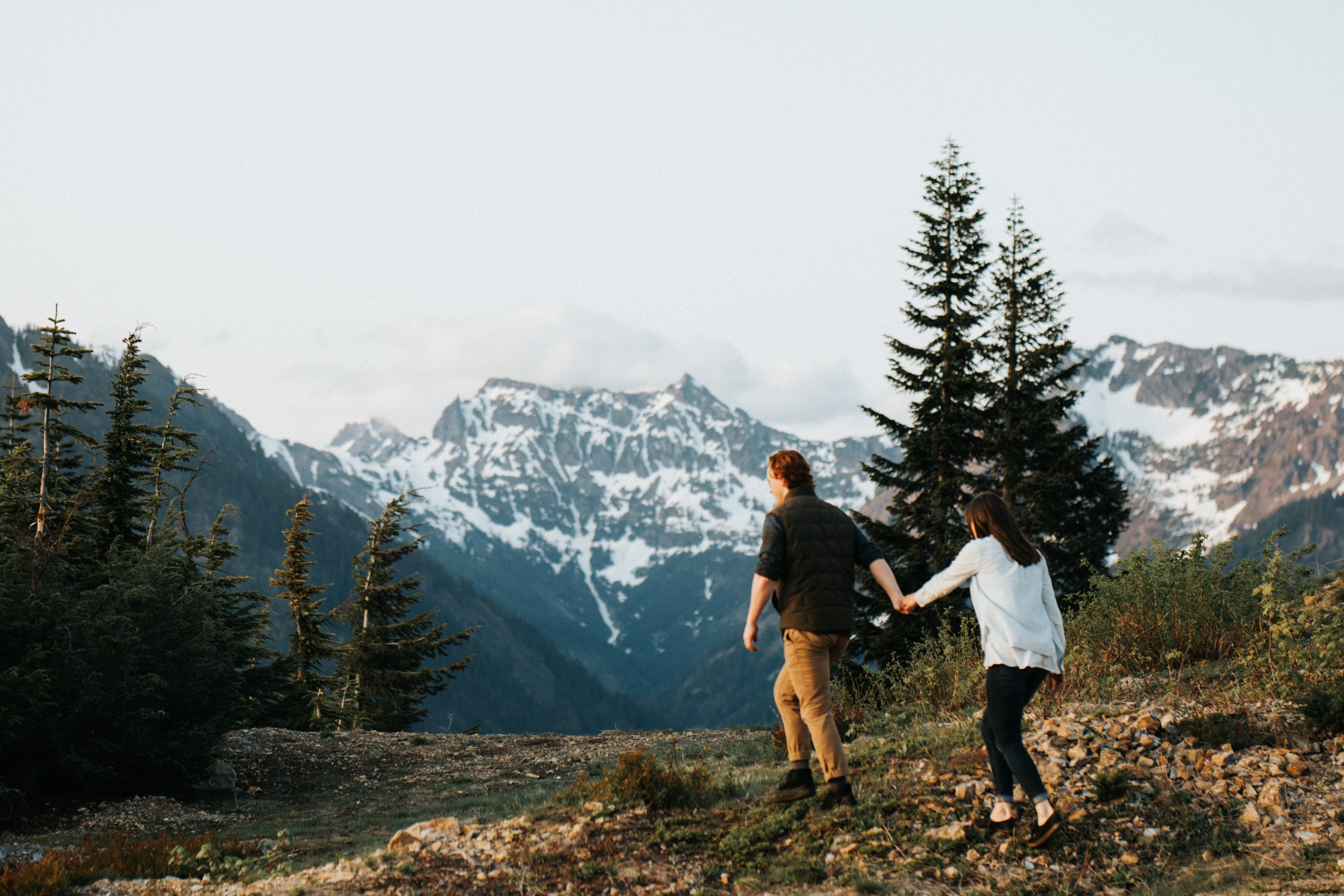 A couple walks together in the mountains during their pnw engagement session at snoqualmie pass