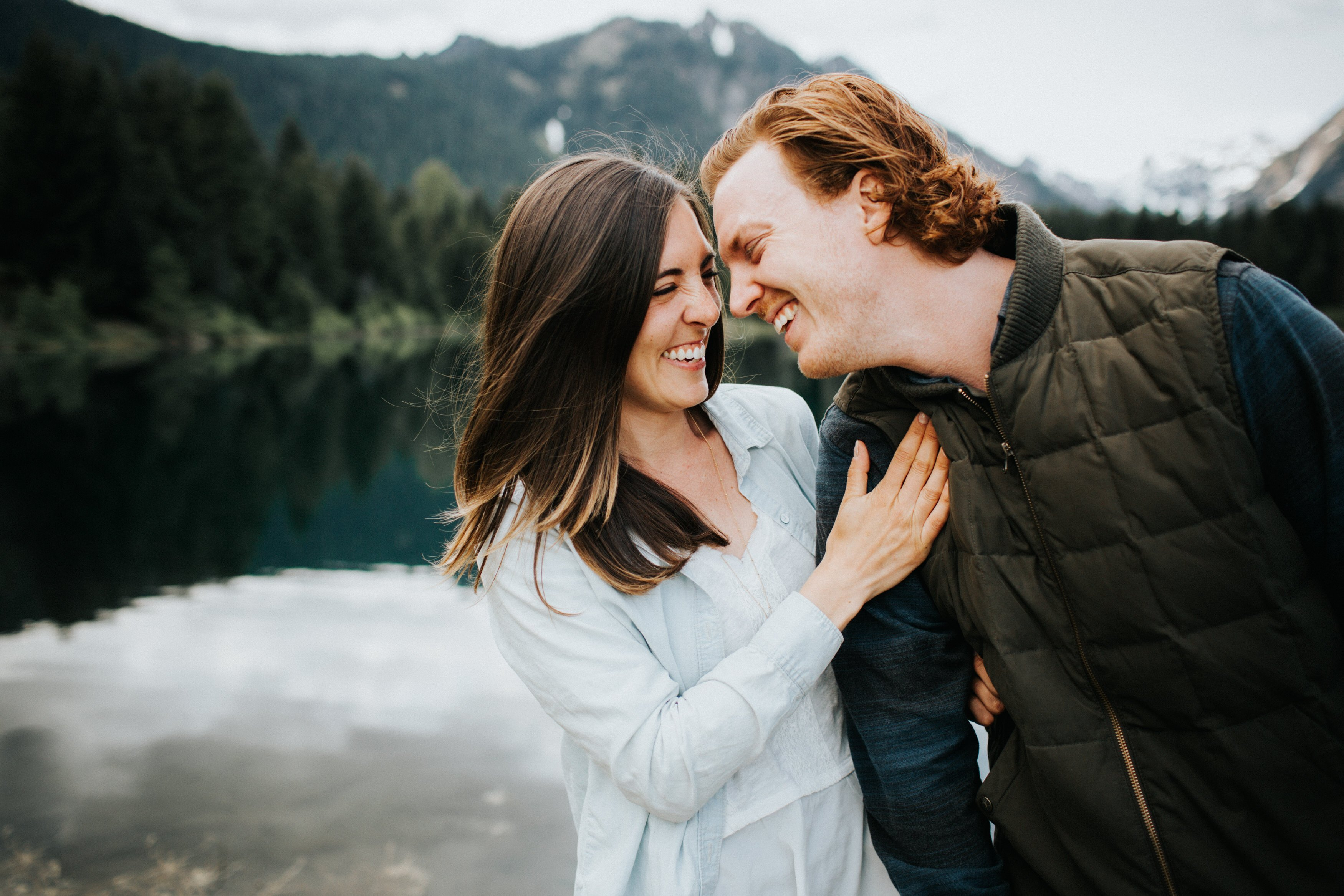 A couple laughs during their engagement session at gold creek pond