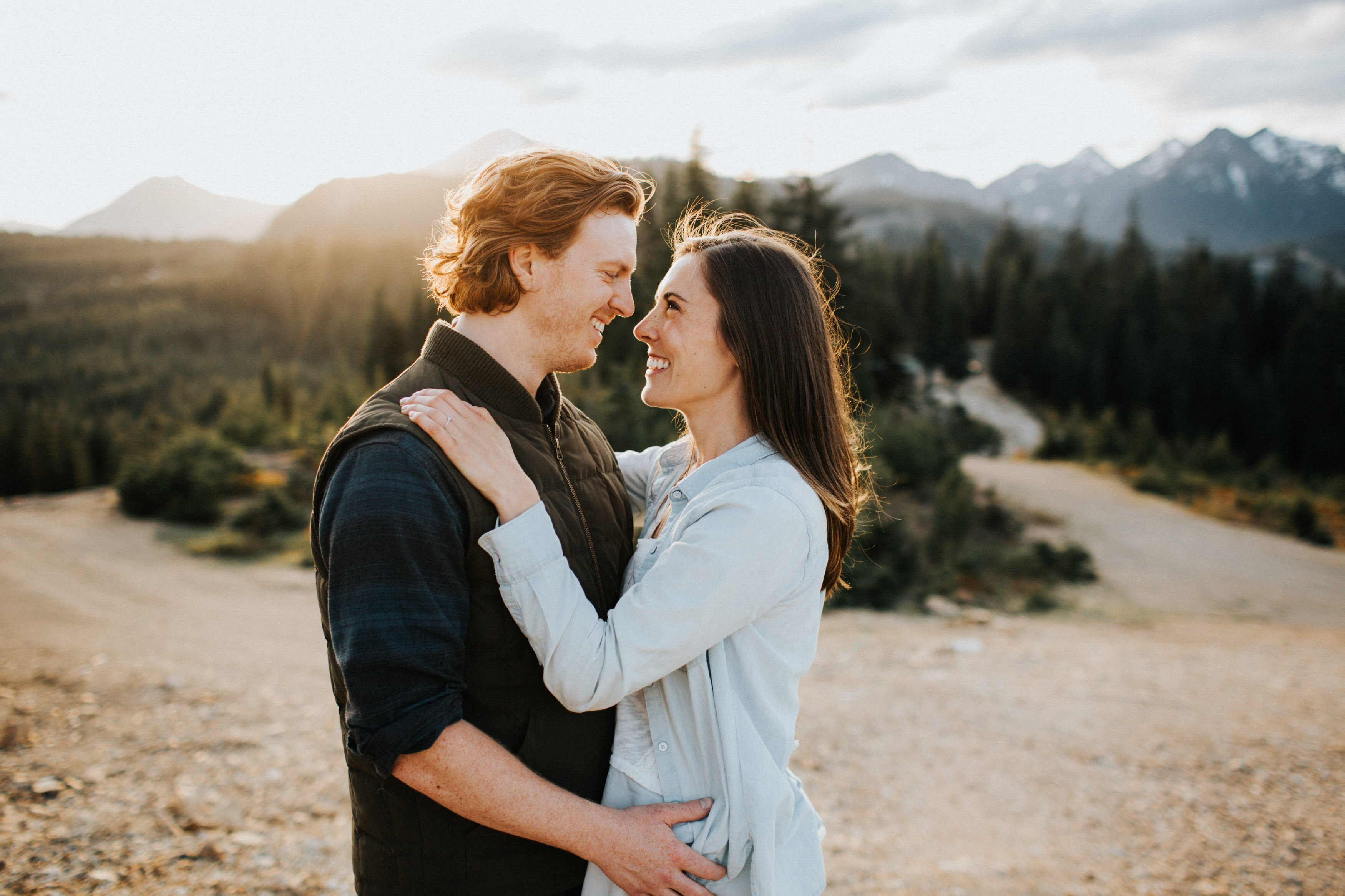 A couple hugs during sunset at their mountain top engagement session
