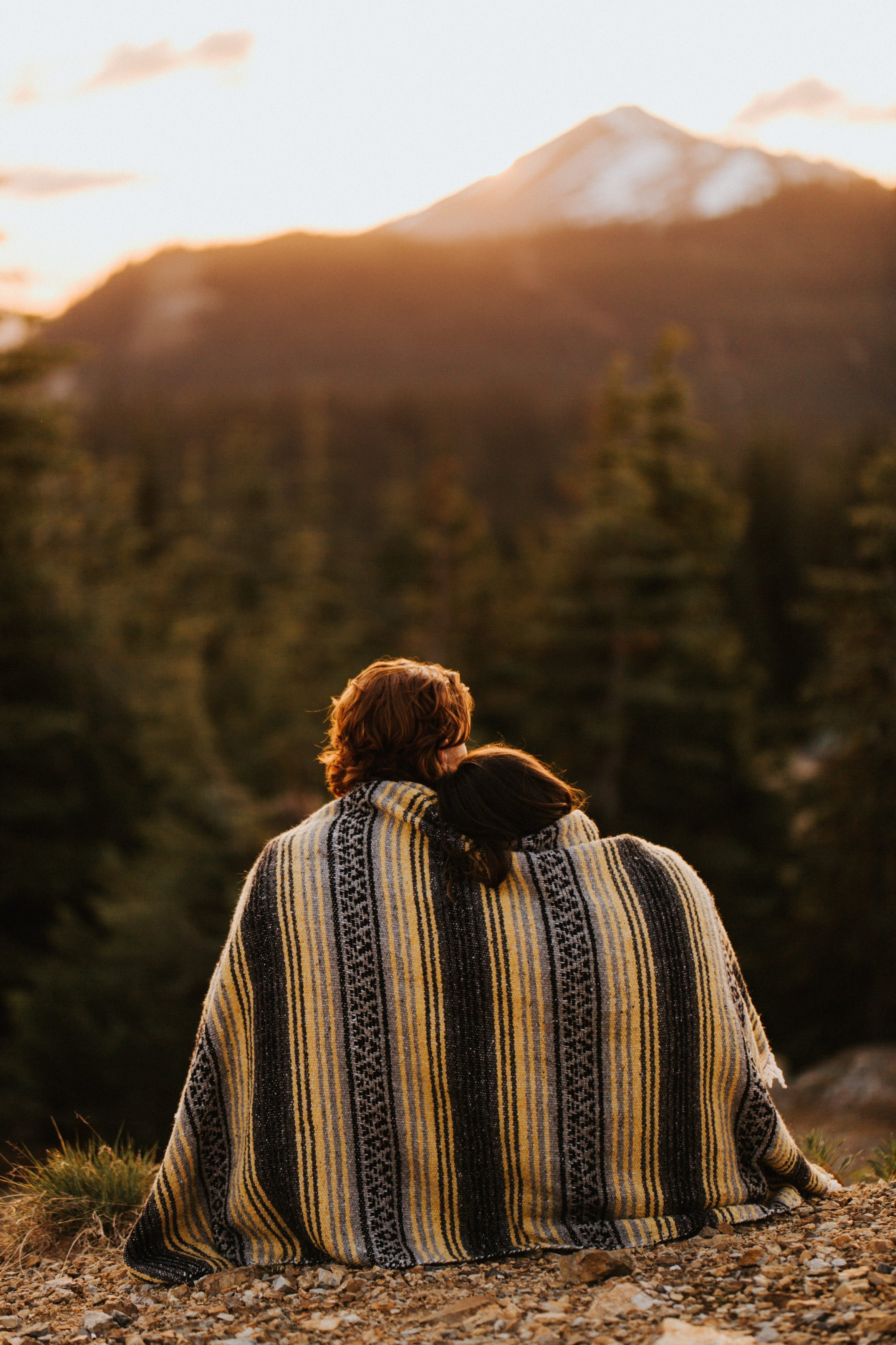 A couple cuddles together under a blanket during their mountain top engagement session
