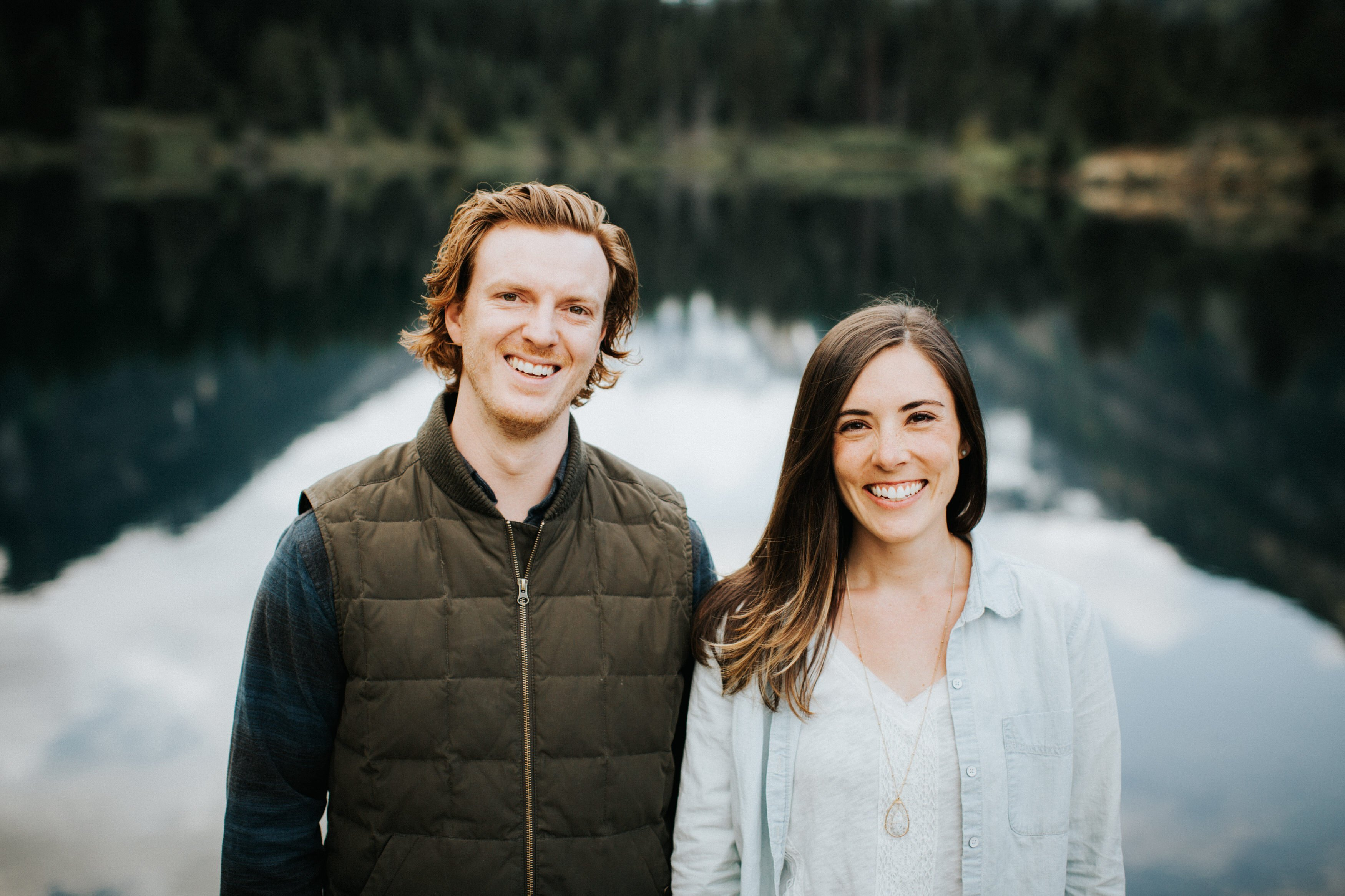 A couple smiles during their engagement session at gold creek pond