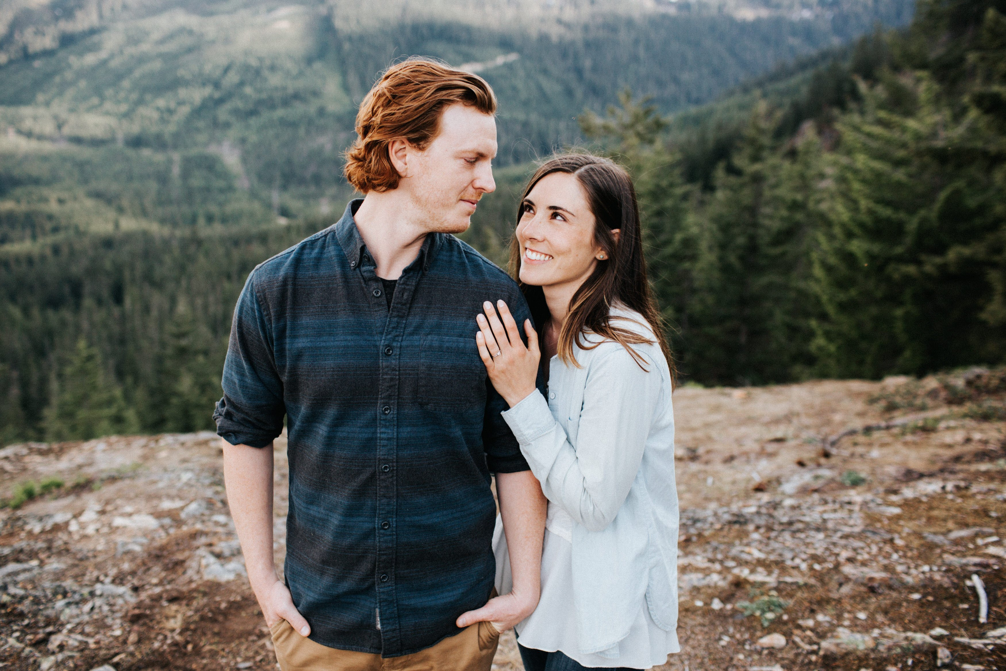 A couple looks at each other and smiles during their engagement session in the mountains