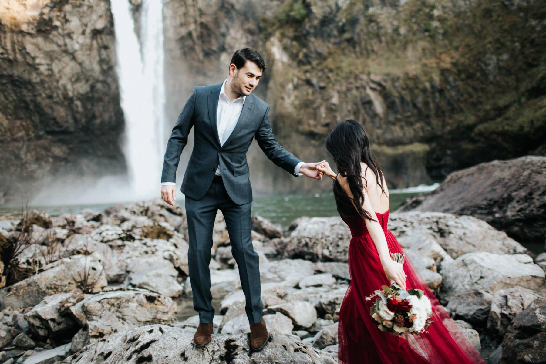 A groom helps his bride at snoqualmie falls