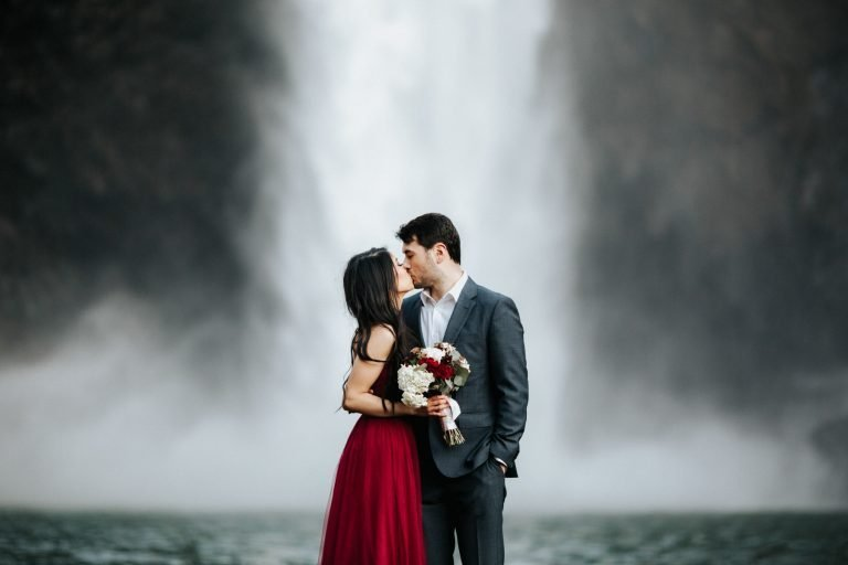 A couple holds each other during their pnw engagement session at snoqualmie falls