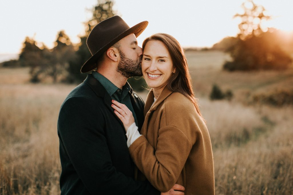 A couple kisses during their engagement session at Discovery Park in Seattle. Shot by Wiley Putnam photography.