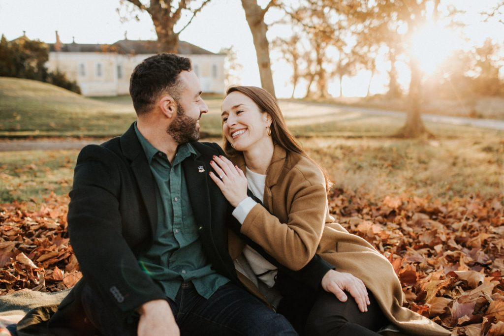A couple hugs on a blanket during their engagement session at Discovery Park.