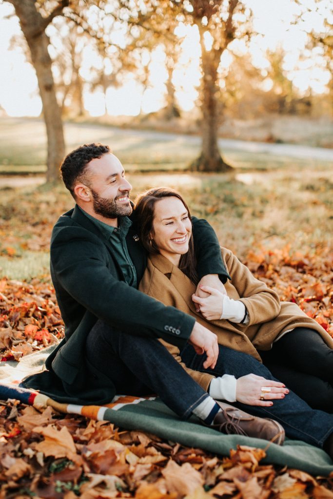 A couple cuddles during their engagement session at discovery park. Shot by Seattle wedding photographer Wiley Putnam.