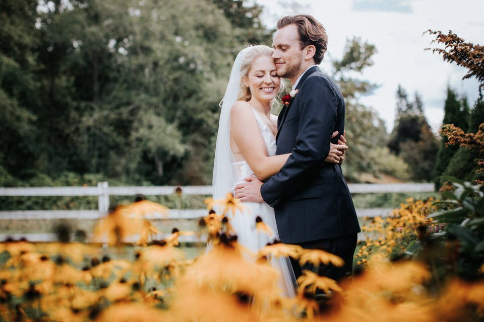 A couple hugs in the flowers at Chateau Lill in woodinville.