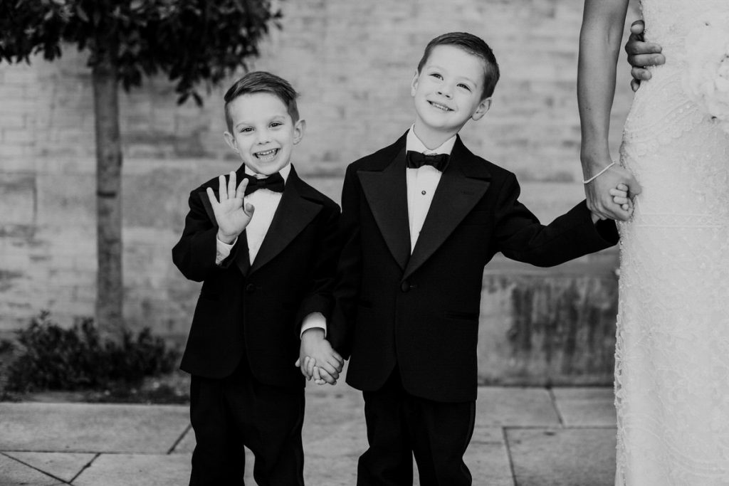 Two ring bearers wave at the camera on a wedding day in Seattle.