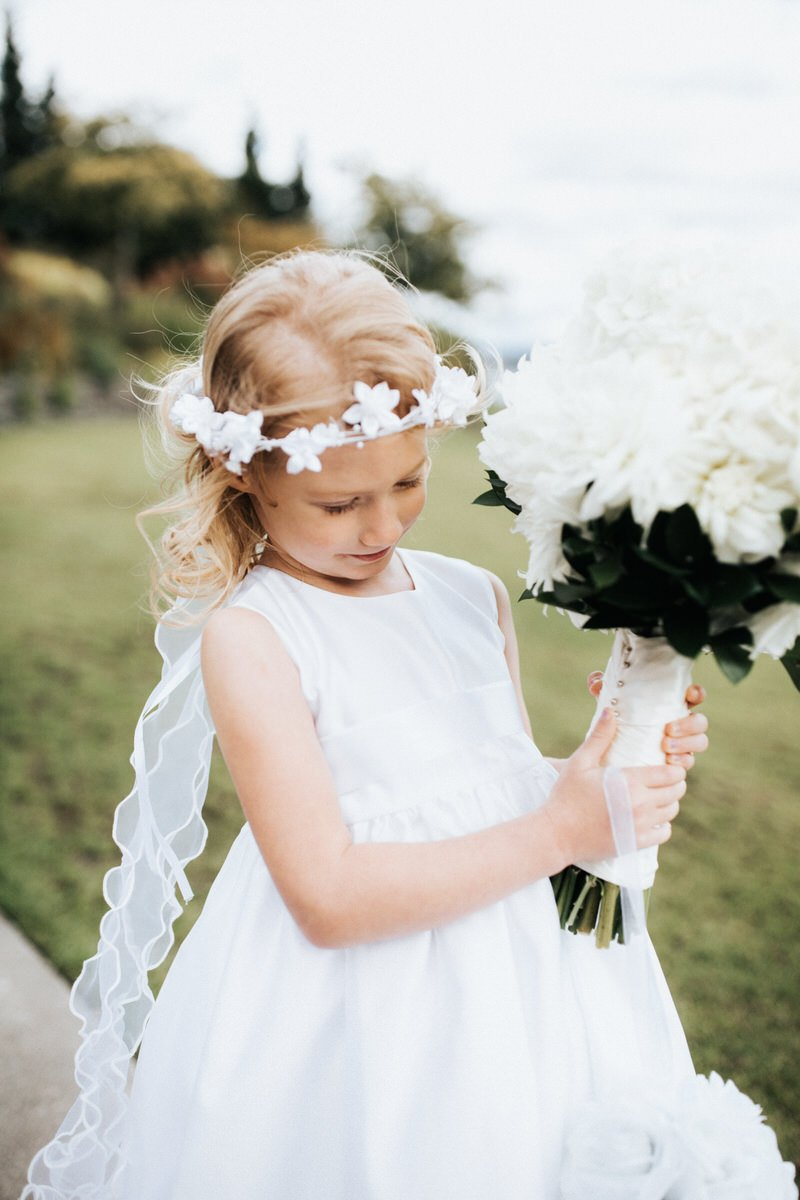 A flower girl looks at the brides flowers during a wedding at the Seattle Tennis Club.