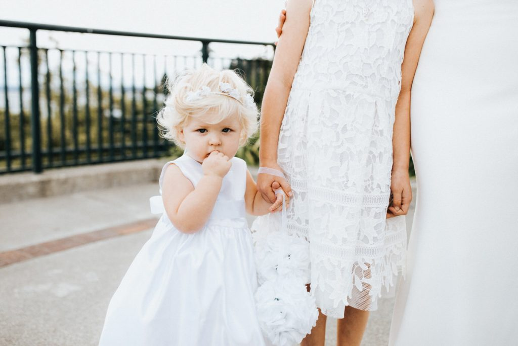 A young girl looks at the camera during a wedding at the Seattle Tennis Club.