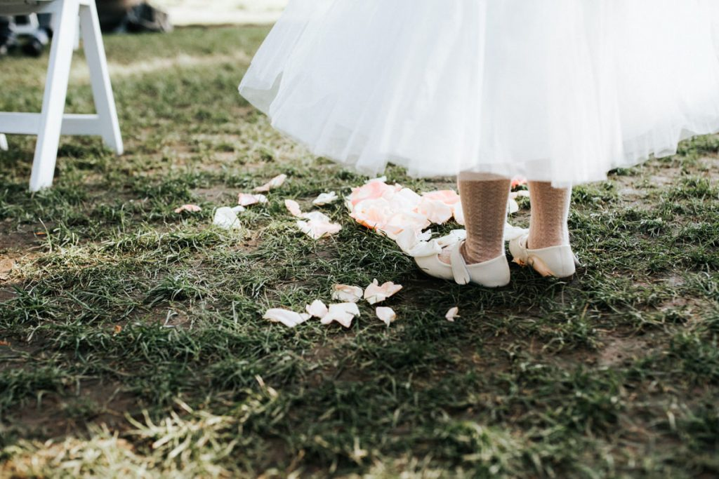 A flower girl and her pedals after dumping them out.