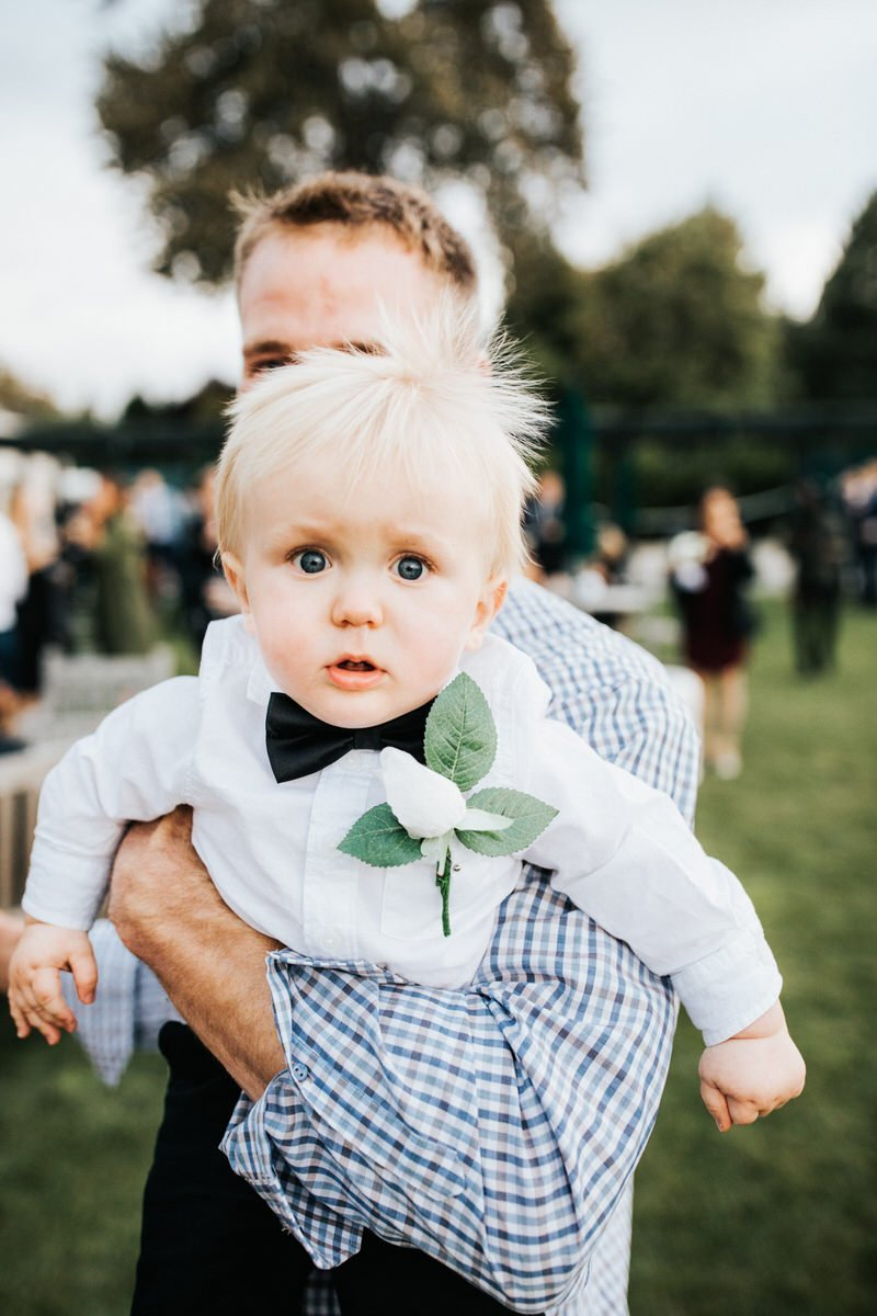 A surprised kid looks at the camera during a wedding at the Seattle Tennis Club.