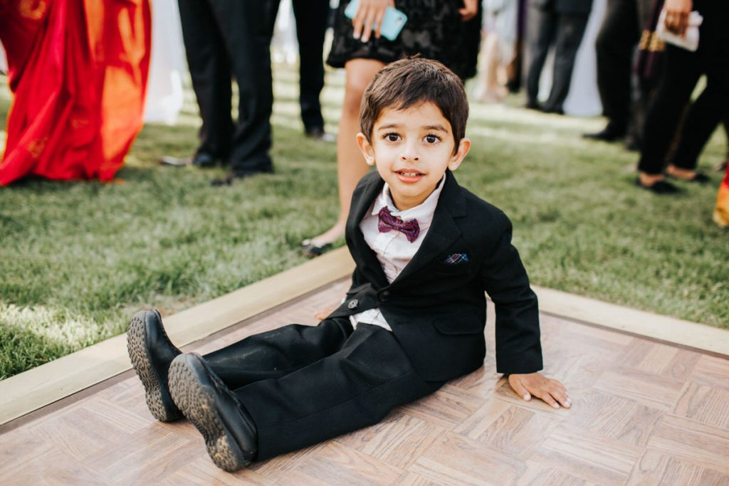 A kid sits on the dance floor at a wedding at Cave B Winery