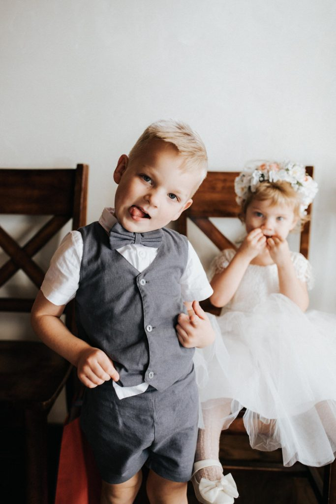 A flower girl and ring bearer make funny faces at the camera.