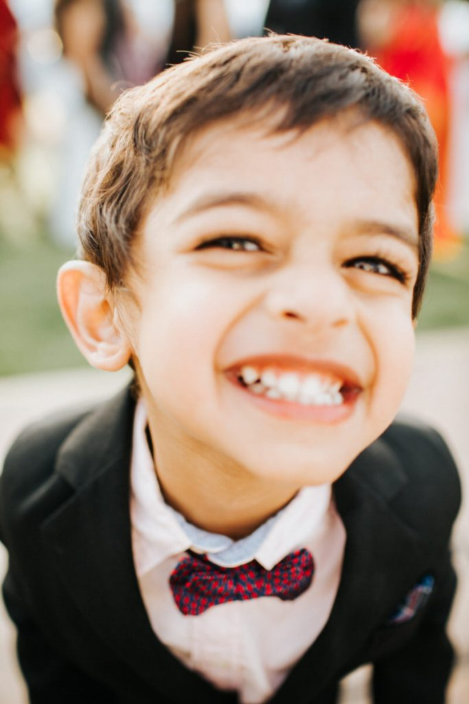 A kid smiles at the camera really close.
