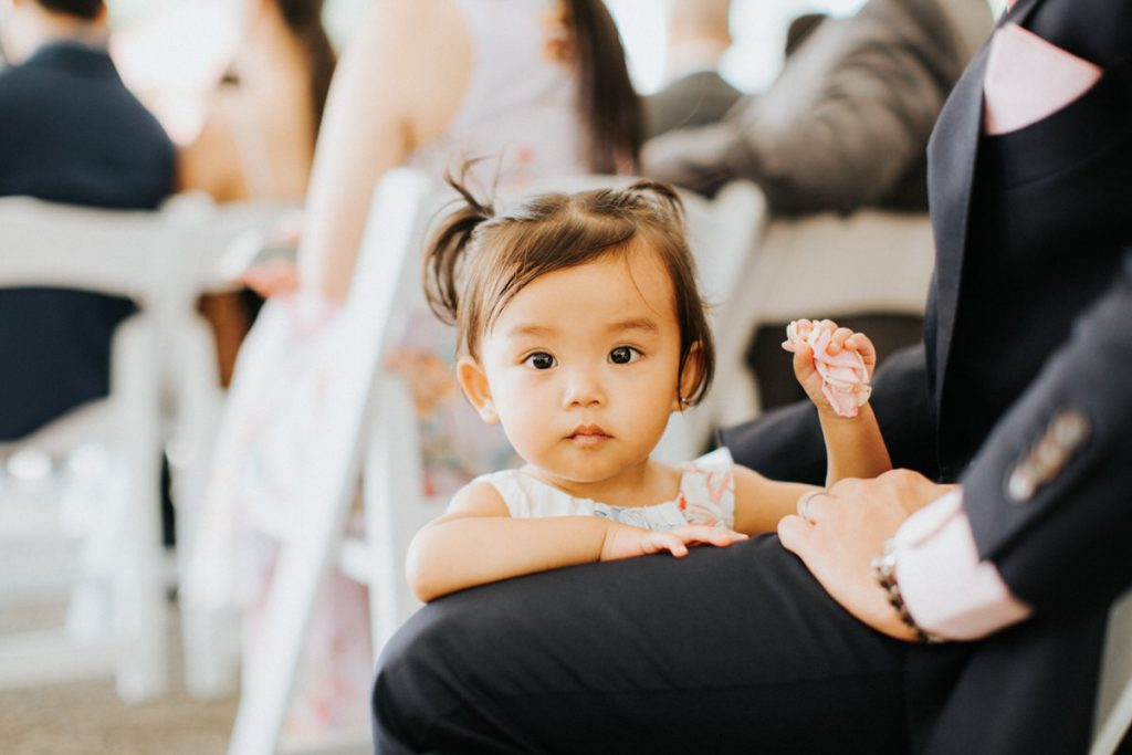 A child looks at the camera during a wedding ceremony.