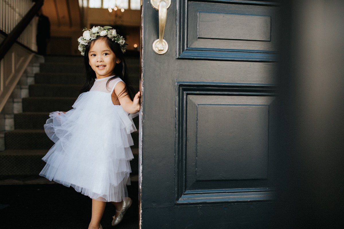A cute flower girl peeks out from behind a door at the Sunset Club in Seattle