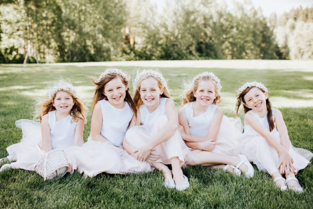 Five flower girls line up and smile for the camera at a wedding.